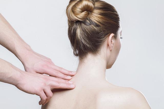 Fisioterapista che massaggia la schiena di una piaziente