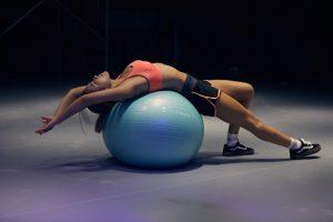 Ragazza che fa pilates usando pallone fisioterapico
