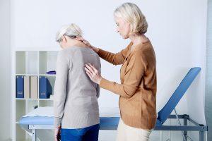 Dottore che visita paziente con dorsalgia